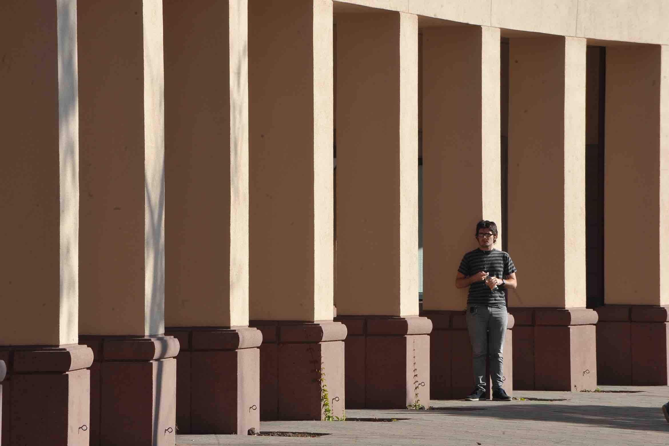 student standing in front of building columns